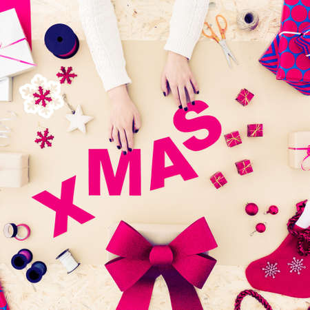 Woman creating pink xmas word on table
