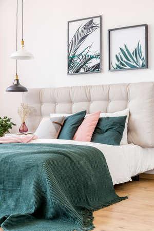 Nahaufnahme von rosa und grünen Kissen auf Bett im Blumenschlafzimmerinnenraum mit Blattposter und Schwarzweiss-Lampe Standard-Bild - 92794289