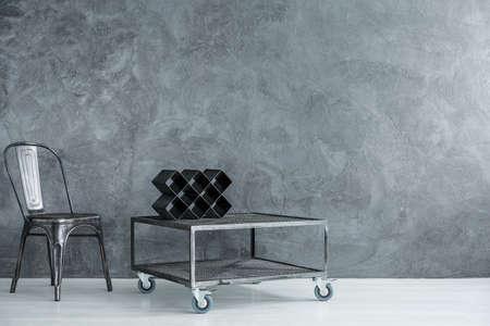 Designer vine shelf on industrial table on wheels in dark room with black chair, copy space interior concept