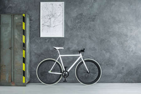 White map in frame on dark concrete wall above white bicycle in dark room with industrial shelf, copy space interior concept