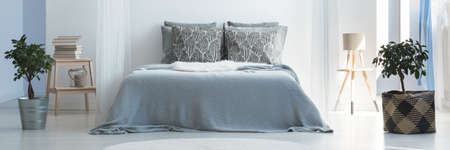 Grey coverlet and patterned pillows on king-size bed in calm bedroom interior with lamp on wooden stool