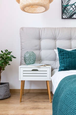 Close-up of glass vase and book on white nightstand between bed with green pillow and plant in simple bedroom interior