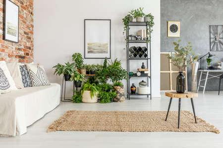 Taburete de madera con jarrón negro sobre alfombra marrón en la luminosa sala de estar con pintura sobre estante con plantas