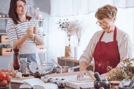 Vrouwen hebben plezier tijdens het koken van traditioneel Italiaans eten op aanrecht met ingrediënten
