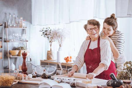 Glimlachende hogere vrouw in rode keukenschort die deeg en kleindochter ontwikkelen die zich achter haar bevinden Stockfoto