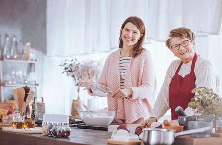 Vrouwen die bij elkaar glimlachen terwijl het maken van pizza in de keuken Stockfoto