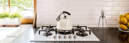 Bouilloire blanche placée sur le poêle dans la cuisine avec des citrons sur le plan de travail