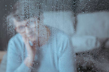 Close-up of raindrops on window with sad senior woman in the background