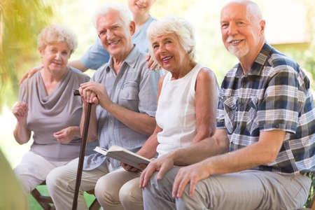Grupo de idosos sorrindo e sentado do lado de fora com um livro Foto de archivo - 92785739