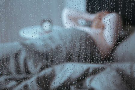Photo through window with raindrops and senior woman with migraine and sleeping disorder in the background Banco de Imagens