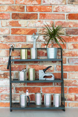 Plant in metal bucket and tools in metal cans on shelf against red brick wall in handymans room
