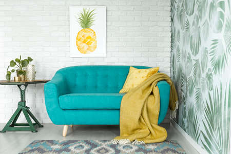 Yellow blanket on blue sofa next to green table with plant in cozy living room with pineapple poster