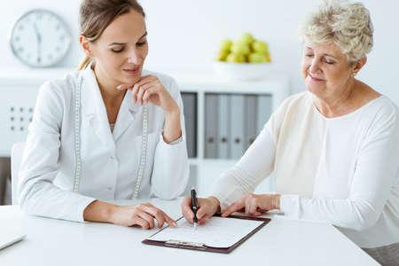病院で毎日の健康的な食事を議論するメジャーテープを持つ栄養士と糖尿病患者 写真素材