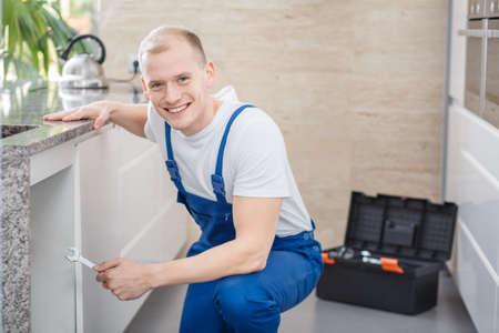 Idraulico professionista sorridente con gli strumenti che riparano un problema tecnico nella cucina Archivio Fotografico - 92949850