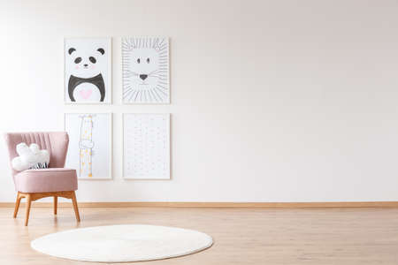 Pink armchair with pillow and white round rug in baby's room with posters on a wall with copy space Stockfoto