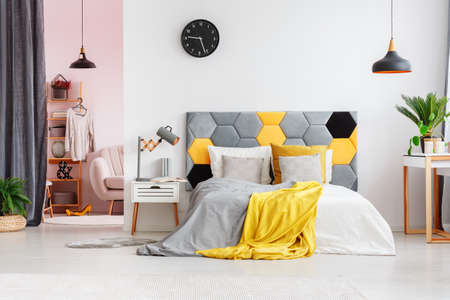 Grey and yellow bedsheets on bed with bedhead against a wall with black clock in modern bedroom interior with wardrobe