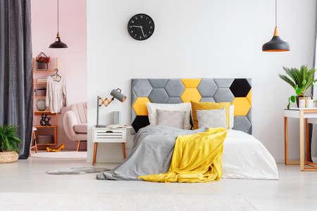 Grijze en gele lakens op bed met bedhead tegen een muur met zwarte klok in modern slaapkamerbinnenland met garderobe Stockfoto - 92950204