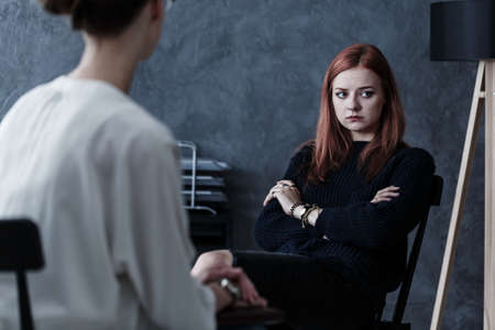 Offended teenager refusing to listen to a counselor during appointment Stock Photo