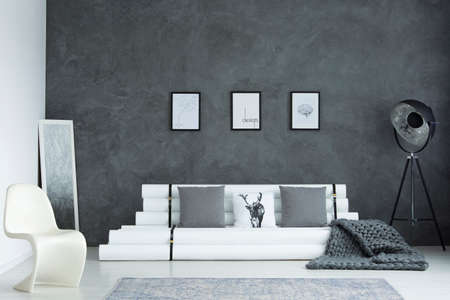 Grey blanket on white settee with pillows in designer interior with modern chair, lamp and mirror Фото со стока