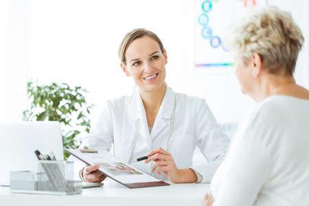 Lächelnder Ernährungswissenschaftler, der dem weiblichen Patienten mit Diabetes einen Plan der gesunden Diät zeigt