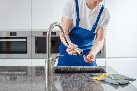 カウンタートップに手袋を持つ台所で蛇口のストレーナーを交換する専門の配管工