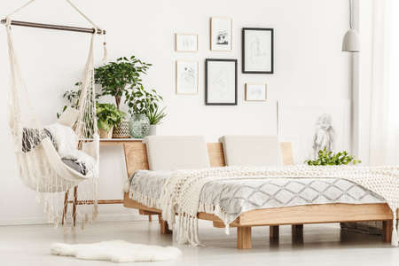 White fur rug next to wooden king-size bed with beige blanket in bright bedroom interior with plants, hammock and posters gallery