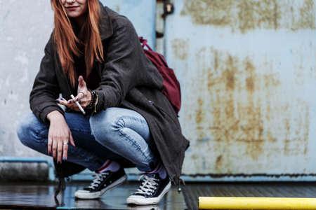 コンクリートの壁にタバコを吸う笑顔の若い女の子のクローズアップ。反抗的な思春期の概念。