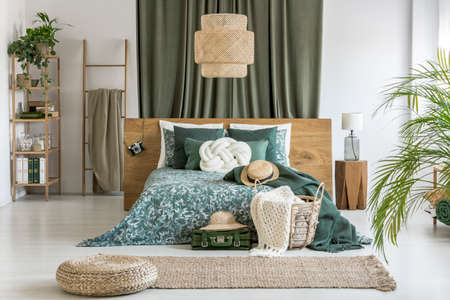 Pouf on a brown carpet in bedroom with rattan lamp and hat on suitcase next to bed with white pillow