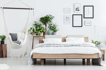 Plants behind wooden bed near hammock with pillows in natural bedroom interior with posters on white wall Foto de archivo