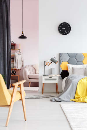 Yellow wooden chair and lamp on white nightstand next to bed in bedroom interior with dressing room and clock on the wall