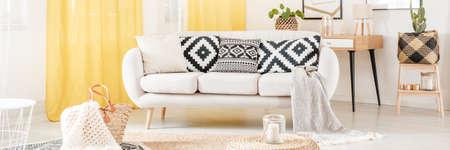Patterned black and white cushions on settee in scandinavian style living room with yellow curtains Stock Photo