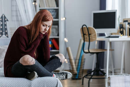 Unhappy young girl with depression and social problem sitting alone on the bed Stock Photo