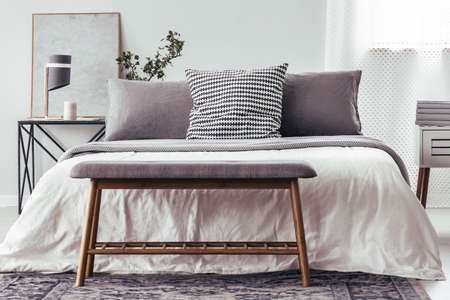 Close-up of wooden bench on carpet against white bed with patterned pillow in bedroom interior with lamp on table Stock Photo
