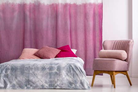 Roze fauteuil met kussen naast bed met blauw beddengoed tegen magenta gordijnen in de slaapkamer van de vrouw Stockfoto