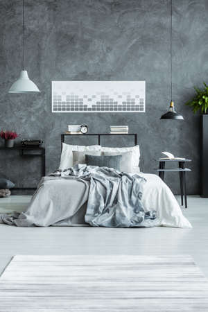 Geometric poster on concrete wall above bed with grey bedsheets in mans bedroom interior with stool, books and desk with typewriter