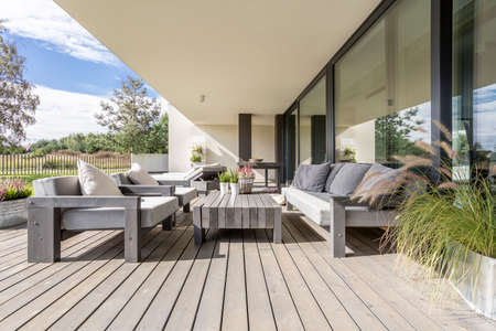 Neat and tidy terrace with wooden garden furniture and plants on table Banco de Imagens