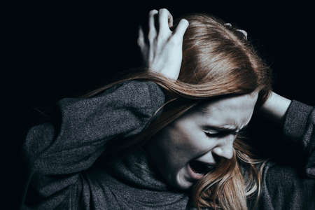 Screaming woman with hallucinations and psychosis against black background Stock Photo - 92950701