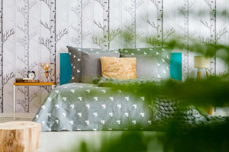 Bright Bedroom With Forest Wallpaper In The Photo With Plant In Blurred  Foreground Stock Photo