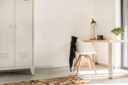 Witte houten stoel met zwarte deken die zich door het bureau met lamp en ingemaakte installatie bevindt