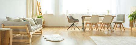 White rug on wooden floor next to a beige sofa in bright dining room with white and grey chairs at table