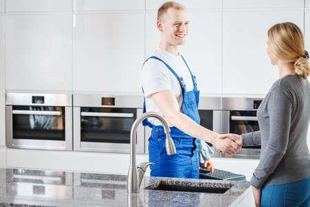 台所の不具合を修復するための笑顔の配管工に感謝の女性 写真素材