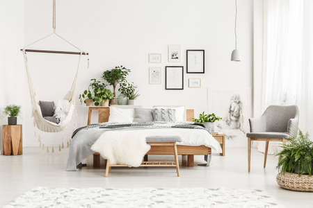 White fur on bench and grey chair in bohemian bedroom interior with hammock, plants and posters
