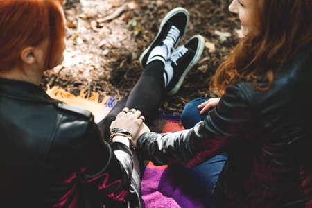 公園で毛布の上に座って手を繋いでいるレズビアンの女の子の高角度