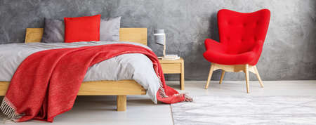 Close-up of red blanket and pillow on wooden bed and armchair in bedroom with concrete wall