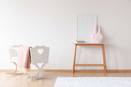 White crib with pink blanket near wooden table with pillow in baby's room with poster and copy space
