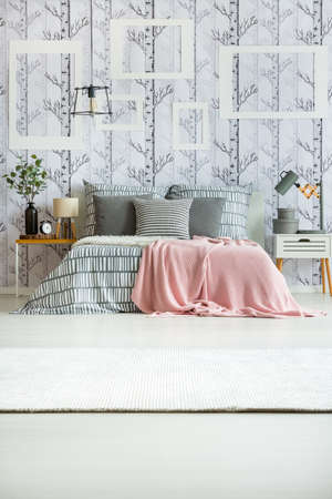 Pink coverlet thrown on king-size bed with patterned bedding and pillows in room with lamps Stock Photo