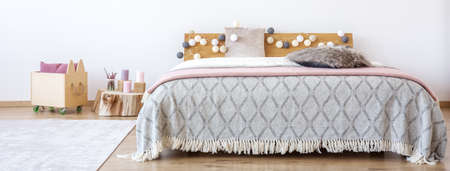 Cotton balls on wooden bedhead of king-size bed with pink blanket in girl's bedroom with crate