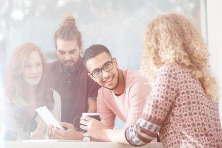 Groep vrienden die en tijdens middagpauze op het moderne kantoor spreken lachen