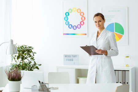 Professional nutritionist in white uniform in the office with plant and colorful posters