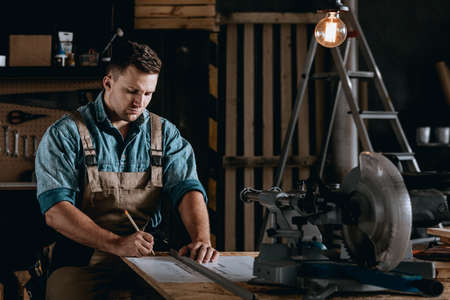 Knap klusjesman die lange uren in zijn atelier werkt en een plan tekent voor een huisrenovatieproject